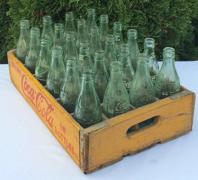 Coca Cola bottles in a yellow crate to rent for barn weddings